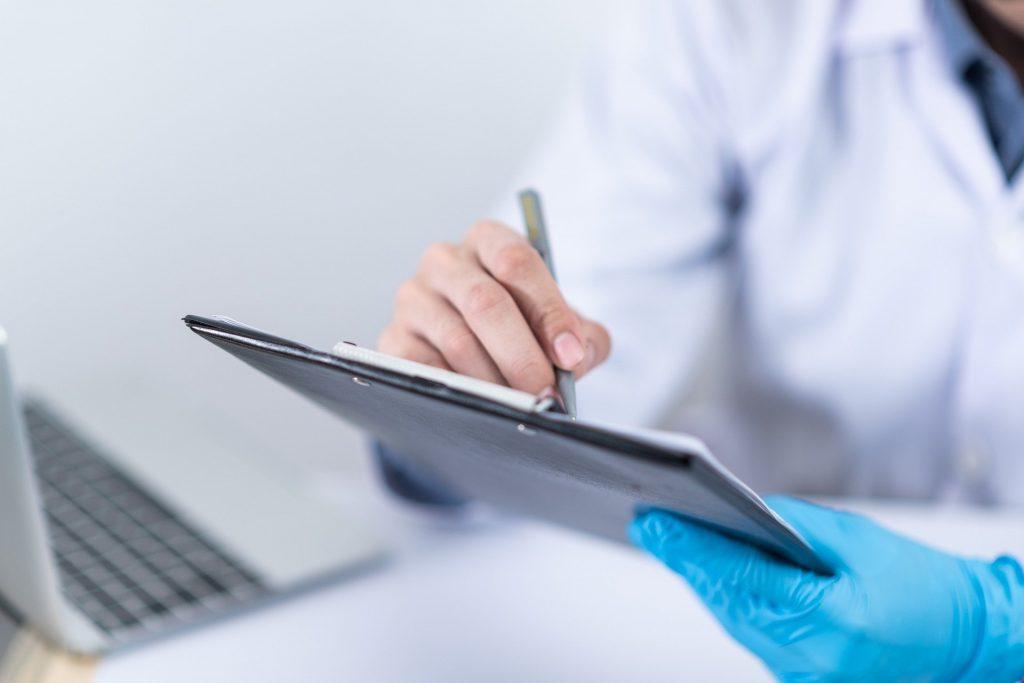 Лекар, преглеждащ данните на пациент преди онлайн консултация