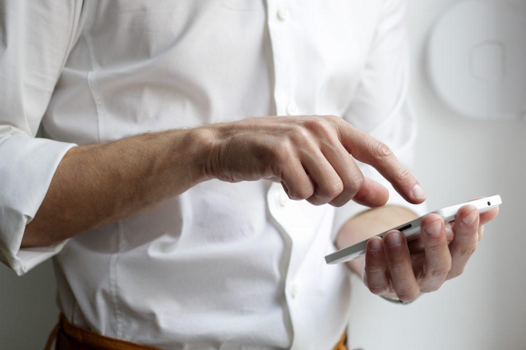 Бизнесмен, който се свързва с преводача си през смартфона